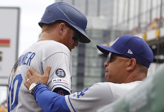 Los Angeles Dodgers manager Dave Roberts greets Justin Turner in the dugout at PNC Park