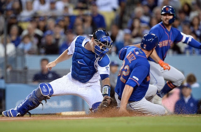 Los Angeles Dodgers catcher Will Smith applies a tag at home plate during a game against the New York Mets