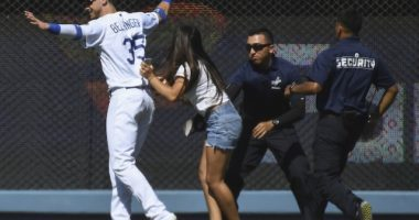 Los Angeles Dodgers right fielder Cody Bellinger is rushed by a fan on the field at Dodger Stadium