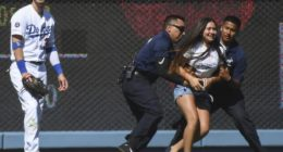 Los Angeles Dodgers right fielder Cody Bellinger is hugged by a fan on the field at Dodger Stadium