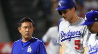 Los Angeles Dodgers manager Dave Roberts and a team trainer walk off the field with Corey Seager after his hamstring injury