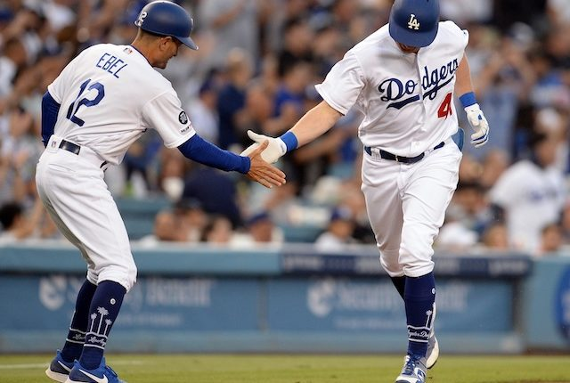 Los Angeles Dodgers third base coach Dino Ebel greets Kyle Garlick after his first career home run