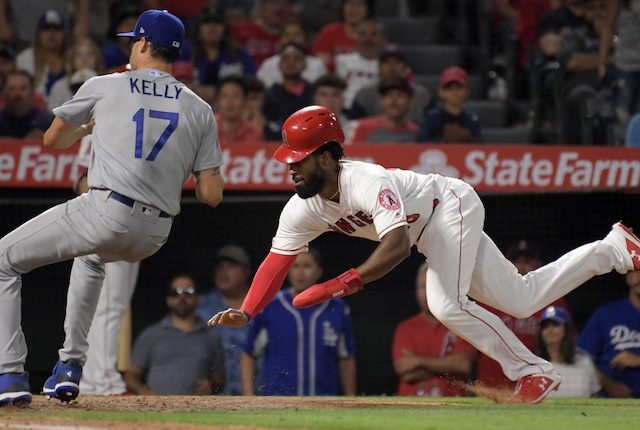 Los Angeles Dodgers relief pitcher Joe Kelly covers home plate after throwing a wild pitch