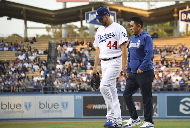 Starting pitcher Rich Hill walks off the field with a Los Angeles Dodgers trainer