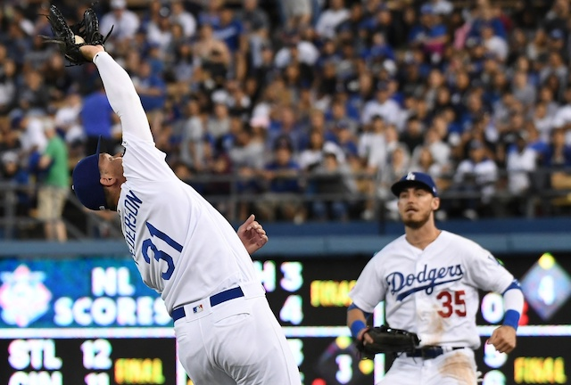 Los Angeles Dodgers right fielder Cody Bellinger watches Joc Pederson make a catch at first base