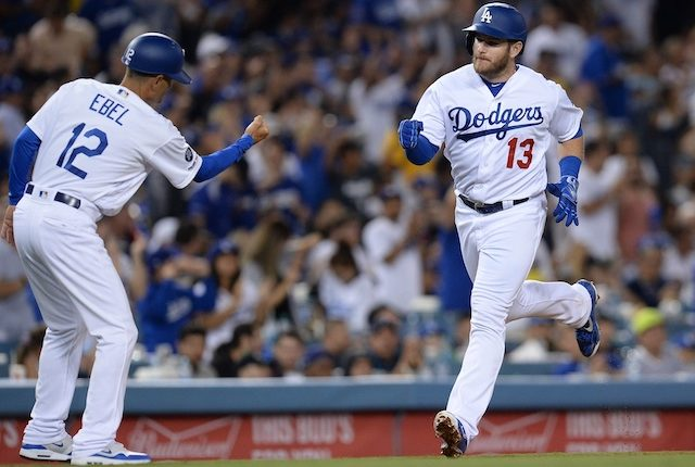 Los Angeles Dodgers third base coach Dino Ebel celebrates with Max Muncy after a home run