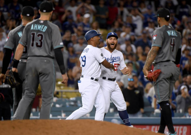Los Angeles Dodgers first base coach George Lombard restrains Russell Martin