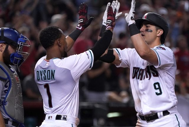 Los Angeles Dodgers catcher Russell Martin looks on as Arizona Diamondbacks teammates Jarrod Dyson and Josh Rojas celebrate after a home run