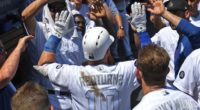 Los Angeles Dodgers teammates Max Muncy and Justin Turner are congratulated in the dugout