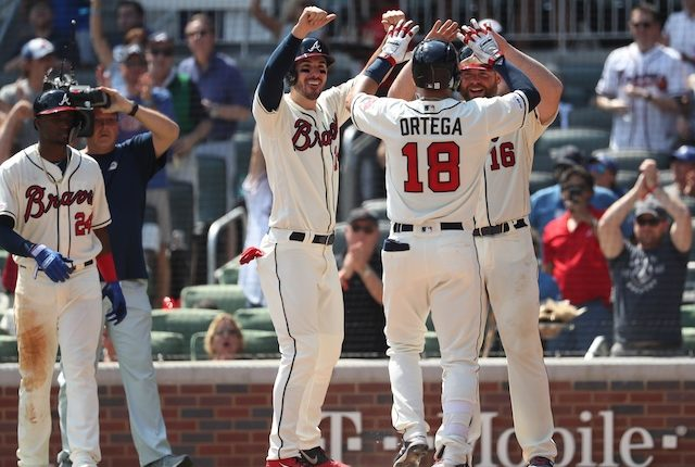 Atlanta Braves teammates celebrate after Rafael Ortega's grand slam against the Los Angeles Dodgers