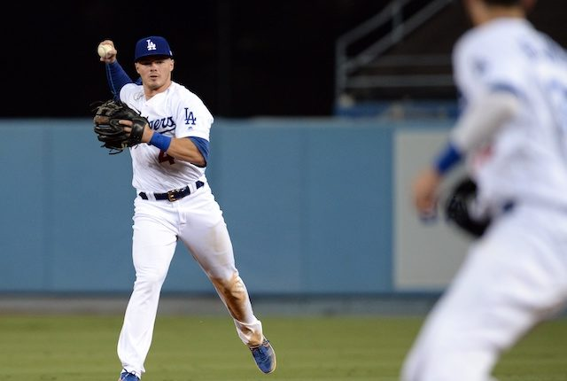 Los Angeles Dodgers infielder Gavin Lux throws the ball to Cody Bellinger