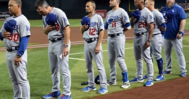 Los Angeles Dodgers manager Dave Roberts, bench coach Bob Geren, first base coach George Lombard, third base coach Dino Ebel and Justin Turner lined up for the national anthem