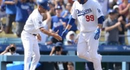 Los Angeles Dodgers third base coach Dino Ebel congratulates Hyun-Jin Ryu after his home run