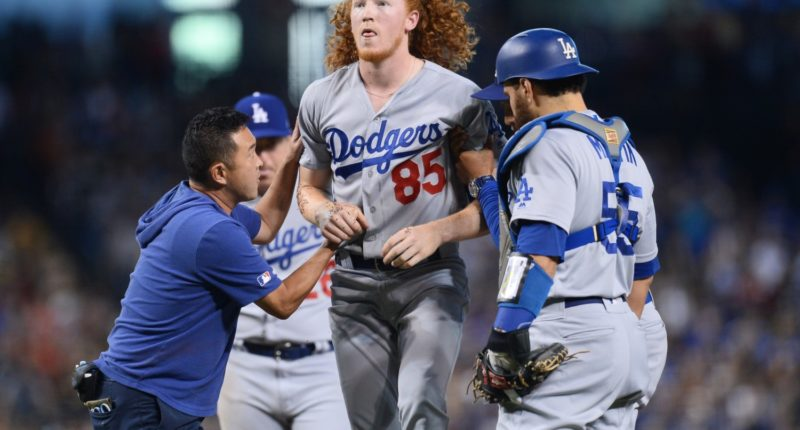 Los Angeles Dodgers pitcher Dustin May is helped to his feet after being hit by a line drive