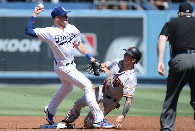 Los Angeles Dodgers infielder Gavin Lux infielder throws the ball to first base