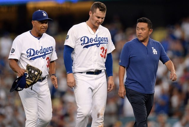 Los Angeles Dodgers manager Dave Roberts and a trainer walk off the field with Joc Pederson