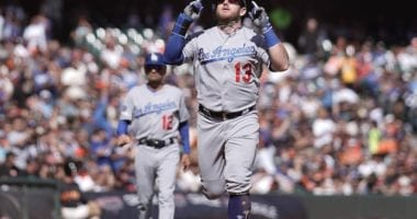 Los Angeles Dodgers third base coach Dino Ebel watches Max Muncy celebrate after a home run