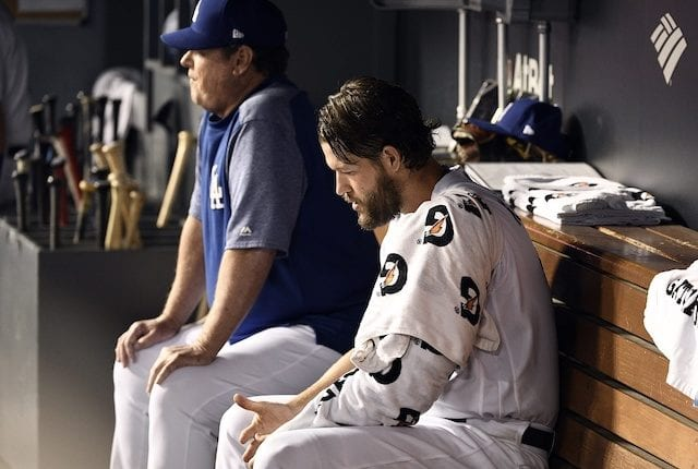 Los Angeles Dodgers pitching coach Rick Honeycutt with Clayton Kershaw in the dugout during Game 2 of the 2019 NLDS