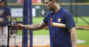 Houston Astros third baseman Alex Bregman looks at his swing on an iPad during batting practice